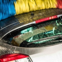 Modern Car in the Automatic Brush Car Wash. Closeup Photo. Vehicle Cleaning.