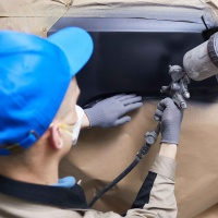 Horizontal close up high angle back view shot of unrecognizable man in uniform painting car body surface