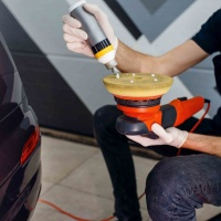 Male worker applies polish on polishing machine, car detailing. Preparation before installation of coating that protects the paint of automobile from scratches. Vehicle in garage, auto tuning